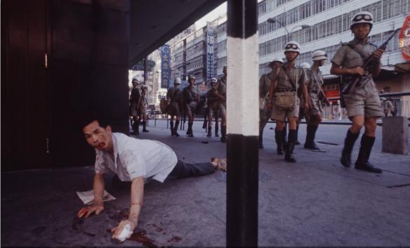 港英「防暴隊」在受傷倒地的工人身邊走過。(來源:Life magazine)