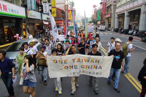 習馬會當天台北街頭的遊行,拉出「ONE TAIWAN, ONE CHINA」標語。(攝影:王顥中)