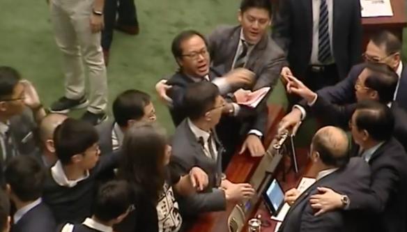 2016年11月2日,香港立法會建制、非建制議員對罵期間,梁繼昌自行倒地的瞬間。用身體保護梁頌恆的梁國雄莞爾一笑。(電視截圖)
